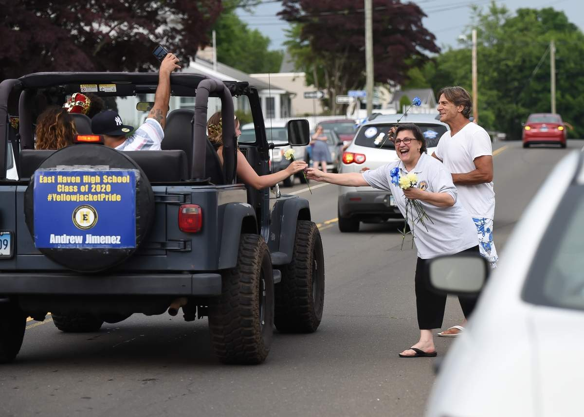 The Town of East Haven celebrated the Class of 2020 with a Motorcade through the town, starting at Town Grove parking lot on Cosey Beach Ave and ending up at the High School Sunday afternoon. Annarose Russo and Michael Perrelli handed out blue and yellow carnations to the seniors as they drove by. Photo by Kelley Fryer/The Courier