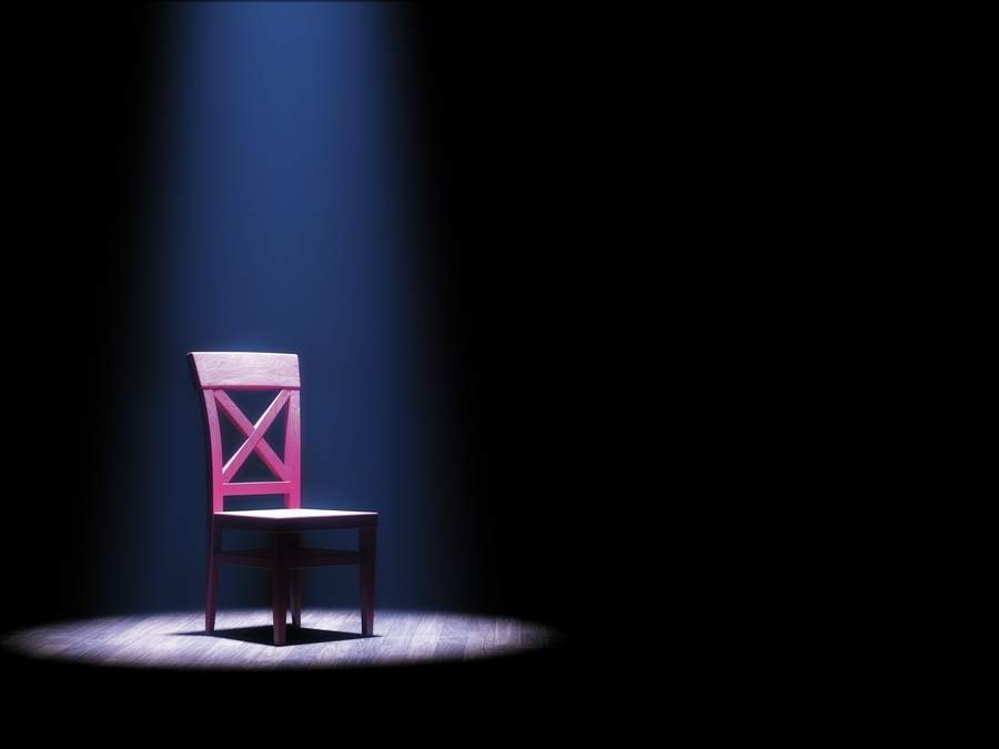 3d illustration of a single empty red chair under a spotlight in anotherwise dark room or on a stage.