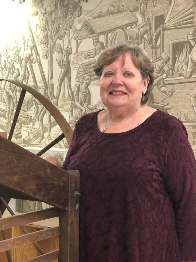 Jane Iannone of the North Haven Historical Society and Museums is excited about the continued renovation of the museums. In the background is a mural by the late Alfred Tulk, a local artist and former society member. Photo by Jason J. Marchi