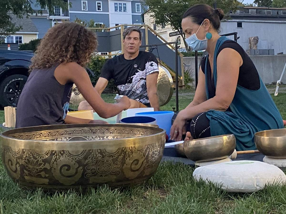 Sean Alexander, center, and Colleen Alexander, right, of Rooted Endurance in Madison, explain how sound bath meditation works at a recent free, public session on the grounds of Moxie restaurant in Madison.  Photo by Pem McNerney/The Source