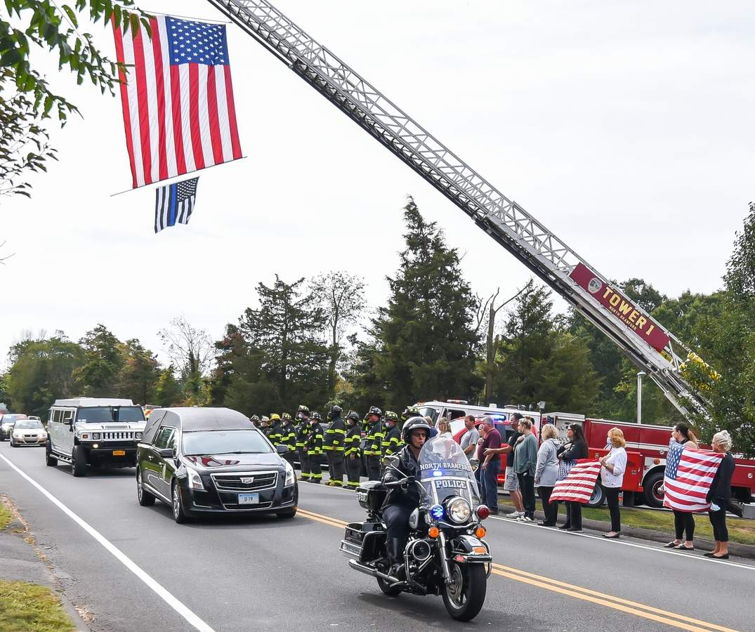 On September 24th at 11:30am a funeral procession for former NBPD Sergeant Christopher Manner passed  members of the North  Branford Fire Department and North Branford Police Department, first responders and members of the community paying tribute in front of the North Branford Police Department along Forrest Rd; from which he retired in 2011 after 25 years of service. Officer Kristen Fitzgerald rode in front of the hearse, in the funeral procession. Photo by Kelley Fryer/The Sound