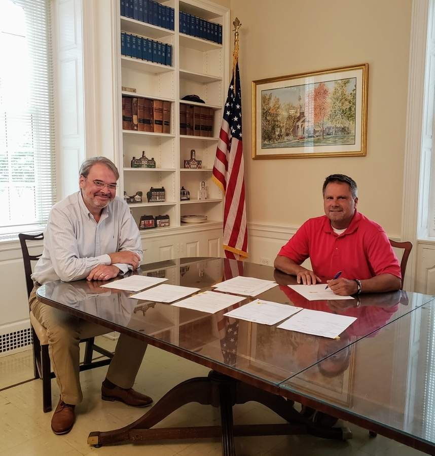 Town Manager Karl Kilduff and Town Council Chair Chris Aniskovich finalize the sale of the old Morgan School property to Greylock Property Group at town Hall on Oct. 5.  Photo by Mary Schettino