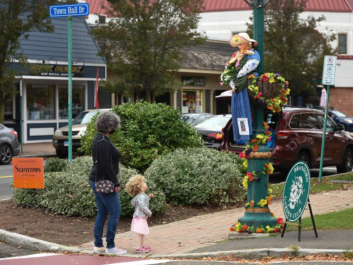 The scarecrows were back on the Branford Green. A mild  Saturday morning was a perfect time to visit the Green, catch up with friends, take a walk and buy a homemade pie from the Branford Garden Club. kathleen Von Hofe and little Elaria Kanor check out he scarecrows along Main St, and Town Hall Dr.  Photo by Kelley Fryer/The Sound