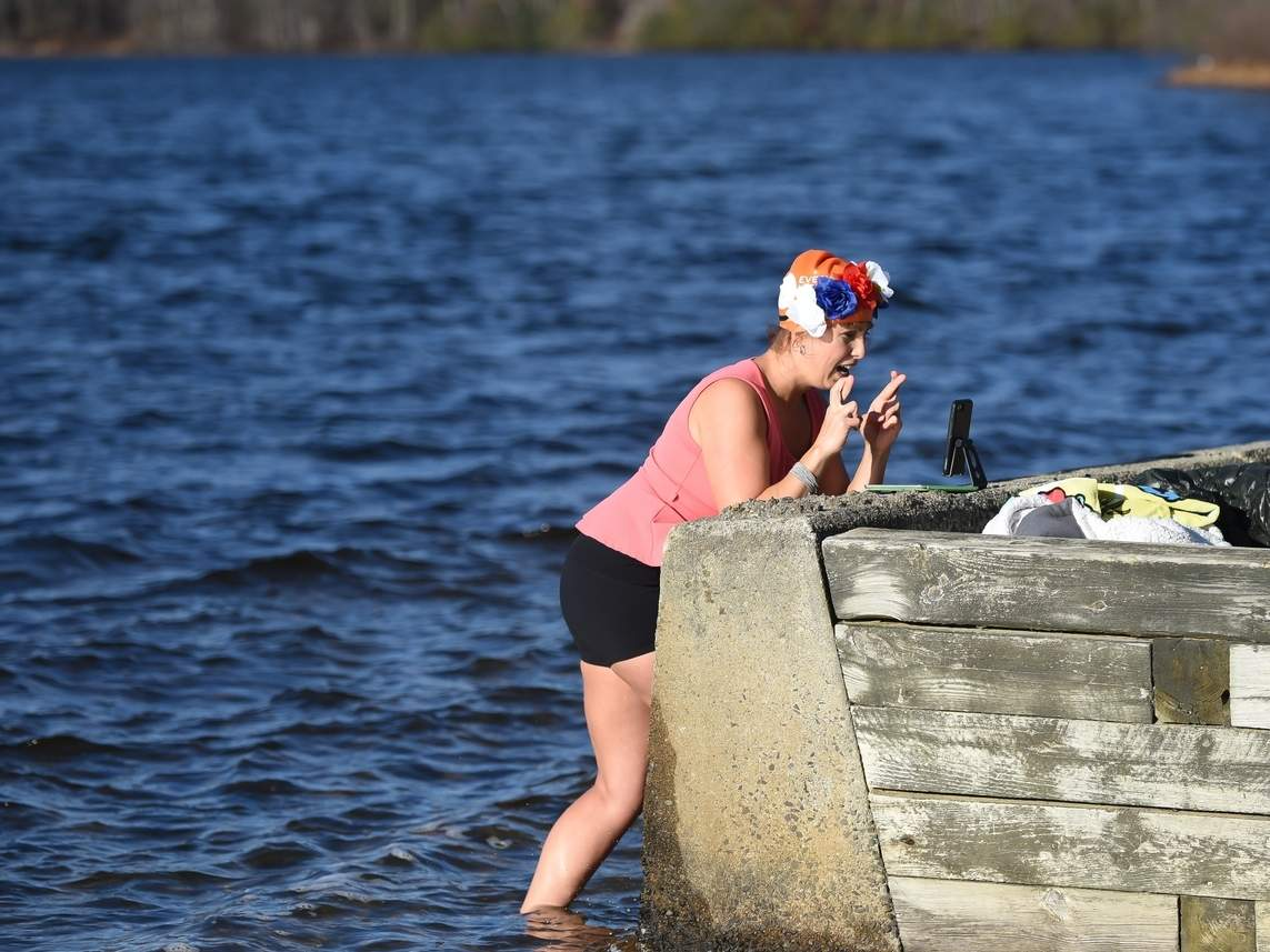 Leah Kisselbrack addresses her livestream audience after a freezing plunge into the cold waters of Cedar Lake on Nov. 15, which raised more than $12,000 for local food programs. Photo by Kelley Fryer/The Courier