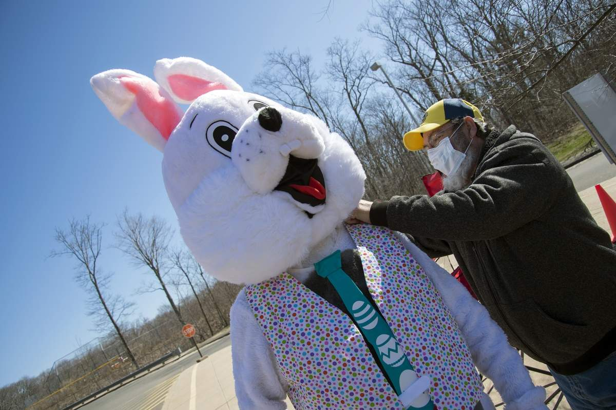 Lions member Les Gorski helps adjust the Easter Bunny´s tie before their drive through event where members handed out bags of Easter candy. The event was held at the H-K Middle School parking lot on April 3, 2021. The drive through event was held as a precaution instead of the annual Easter egg hunt due to Covid-19 precautions.. Wesley Bunnell / Source